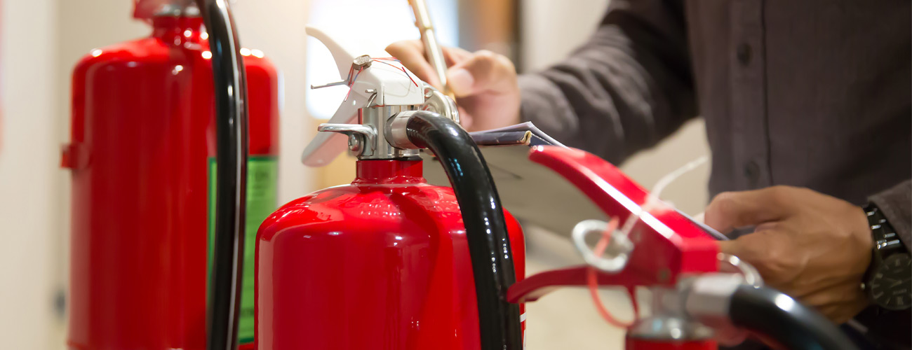 Fire Risk Assessments Bristol. Fire risk assessor examining extinguishers.